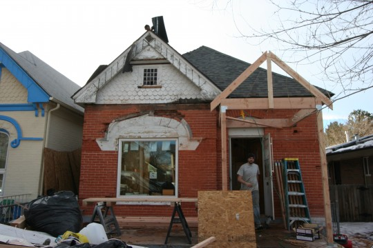 The brick is scraped, the old porch is ripped off, and the new porch is framed